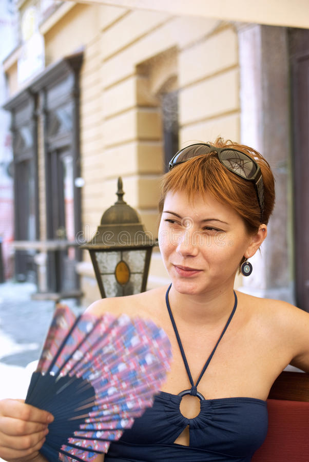 Cool summer. Young woman on a terrace flirting a fan during a hot summer day royalty free stock photography
