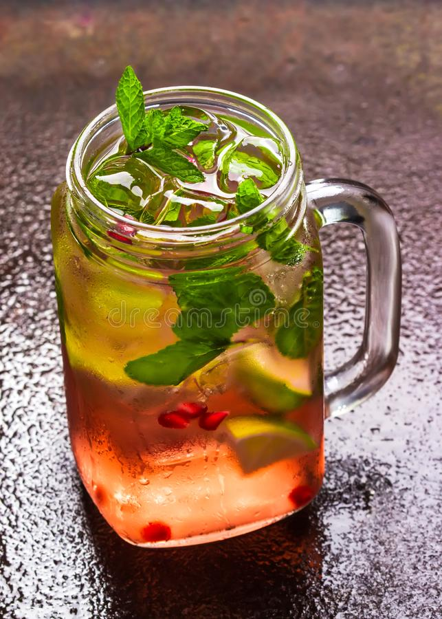 Cool summer cocktail with ice cube, lime, mint leaves, fresh pomegranate juice and pomegranate seeds stock photo