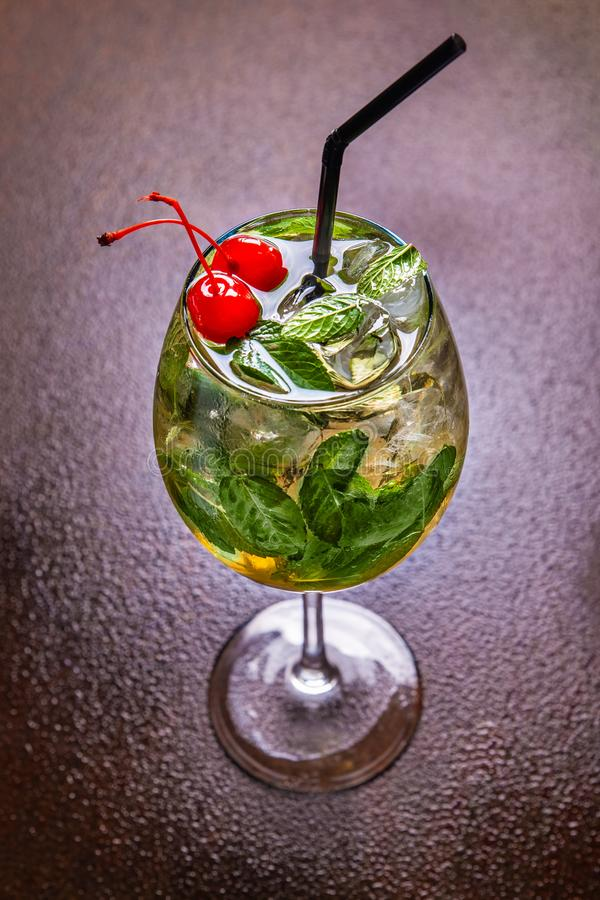 A cool summer cocktail with ice cubes, mint leaves and fresh juice decorated with two cherries. Fresh mint julep stock image