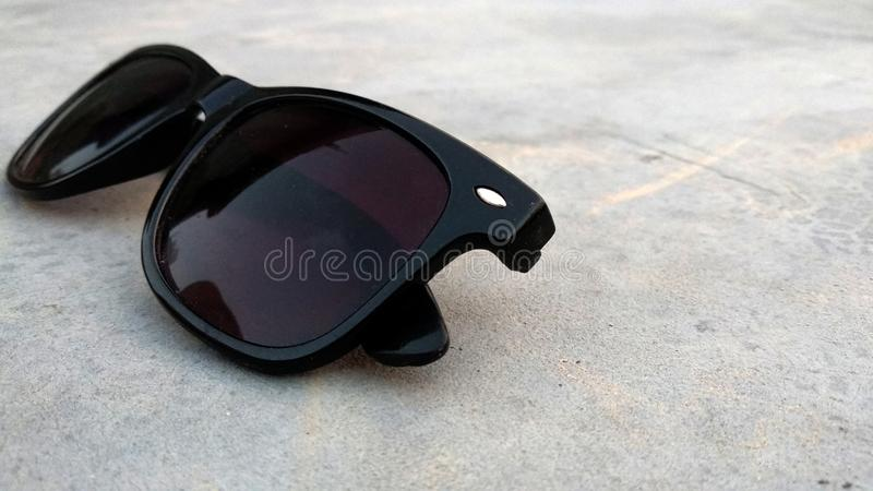 Cool sunglasses with black plastic frame on ground, slanted view from right. royalty free stock photography