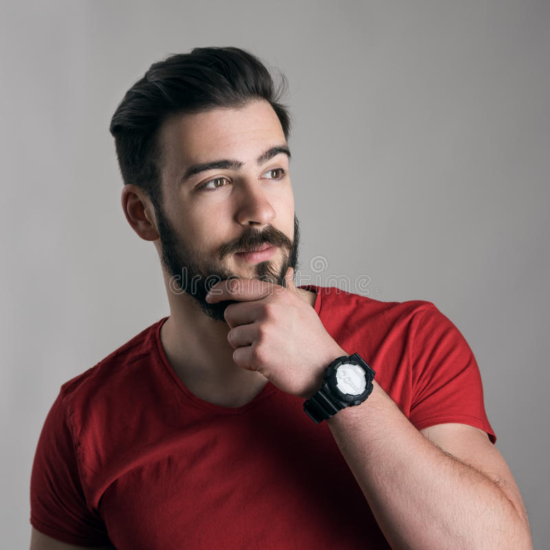Cool thinking young man with hand on chin touching his beard looking away stock image