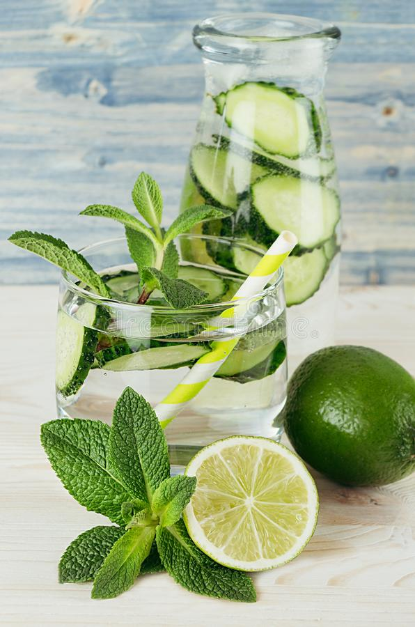 Cool transparent summer lemonade in glass with straw, bottle and ingredients - green cucumber, lime, mint on retro blue wood board. Closeup royalty free stock photo