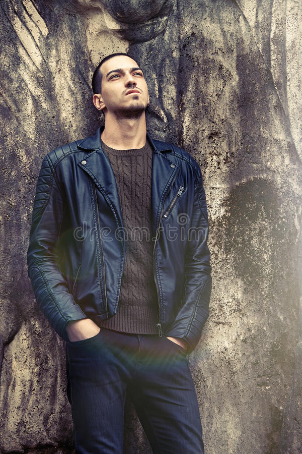Cool trendy man leaning against the wall. Rock style clothing royalty free stock photography