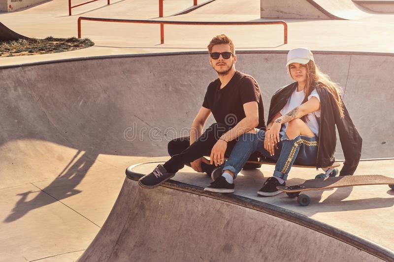 Cool trendy students are sitting at sunny skatepark with their longboards royalty free stock photos