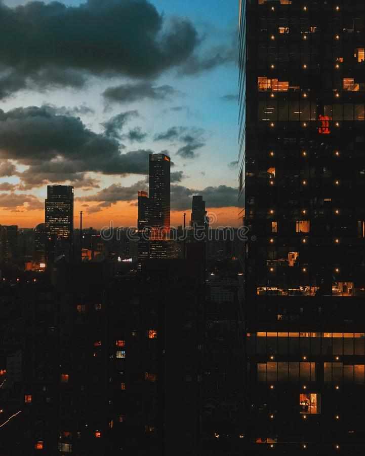 Cool vertical shot of lit-up high-rise buildings in an urban city at sunset with dark large clouds stock photography