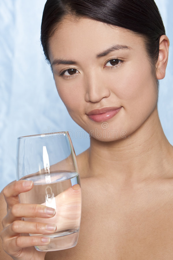 Cool Water. Studio shot of a beautiful young Japanese woman drinking a glass of mineral water stock image