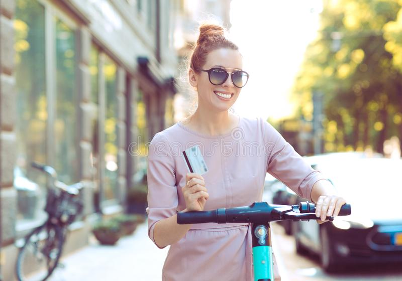 Cool woman with credit card renting an electric scooter ready to explore the city stock image