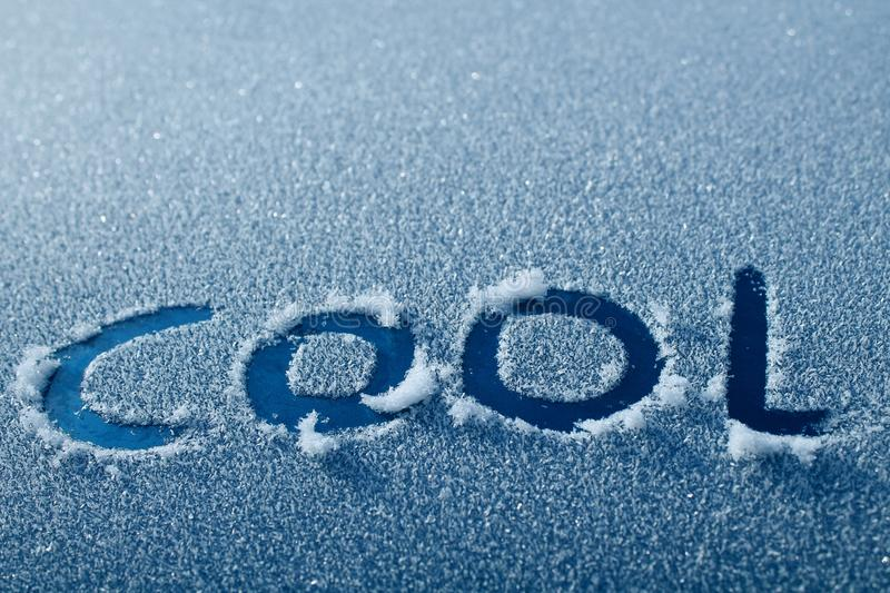 Cool Word in Car Frost. The word COOL written in frost on a blue car stock image