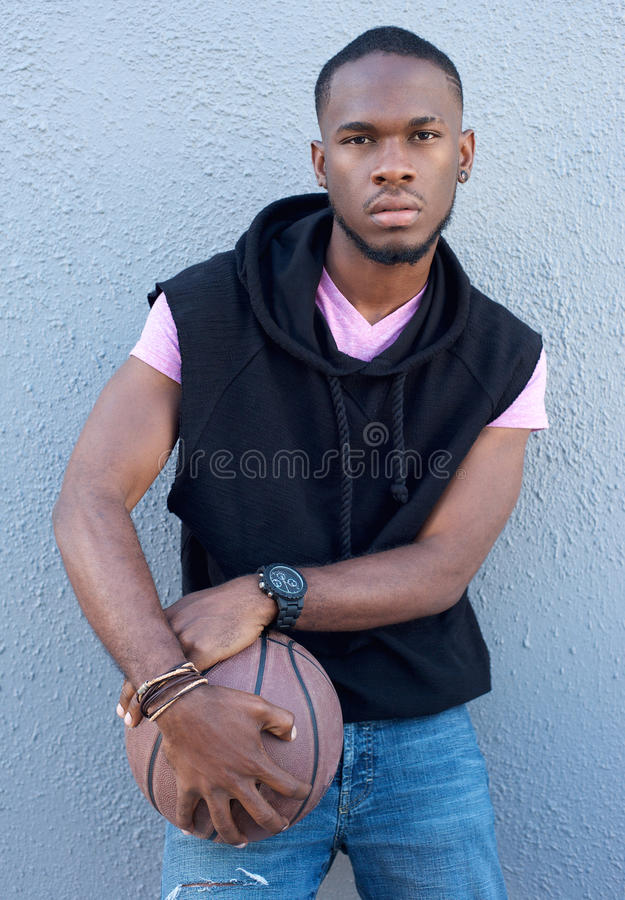 Cool young african american guy holding basketball royalty free stock photography