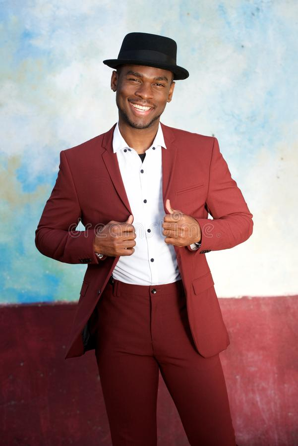 Cool young african american male fashion model smiling with hat and vintage suit by wall royalty free stock photos