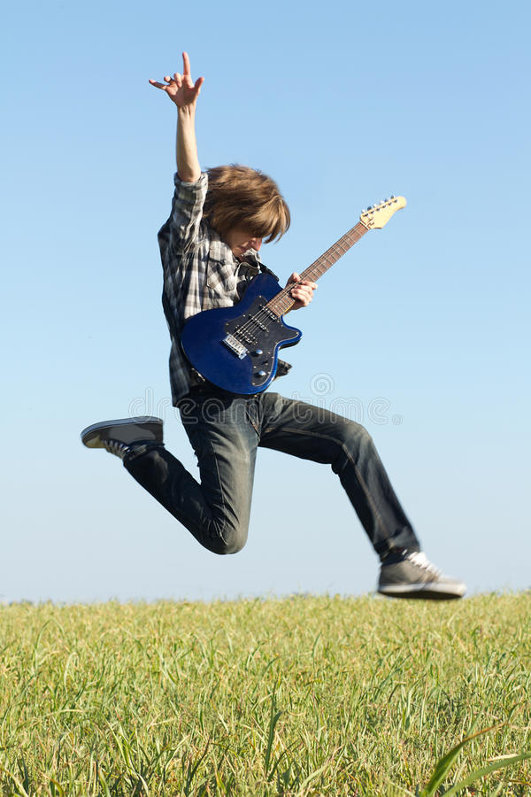 Cool young guitarist jumping royalty free stock images