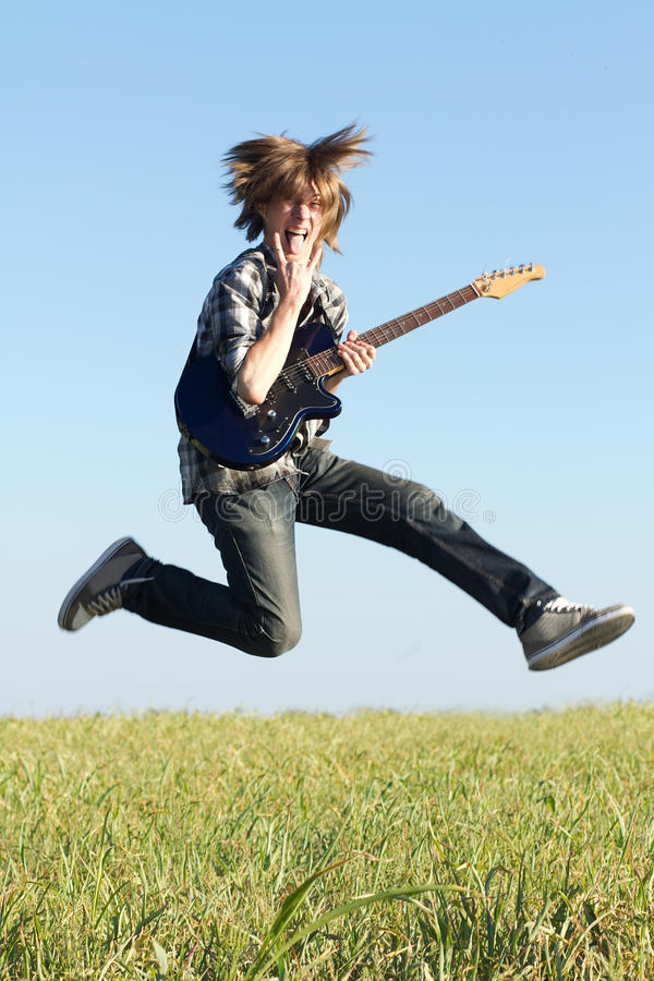 Cool young guitarist jumping stock image