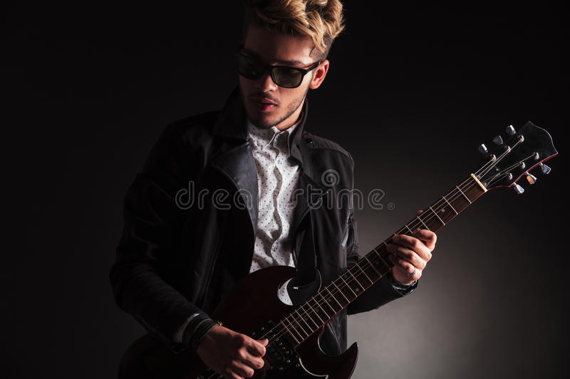Cool young guitarist playing his electric guitar stock image