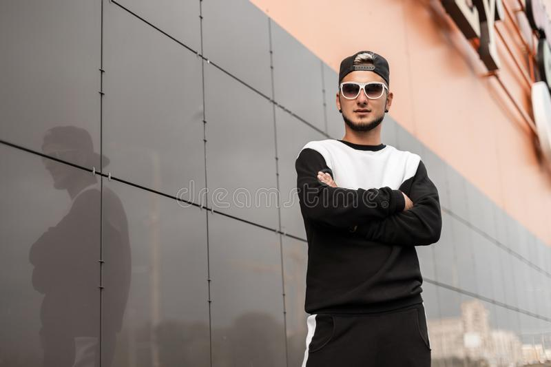 Cool young hipster man in a fashionable black cap in a stylish sweatshirt in vintage white glasses is standing royalty free stock photo