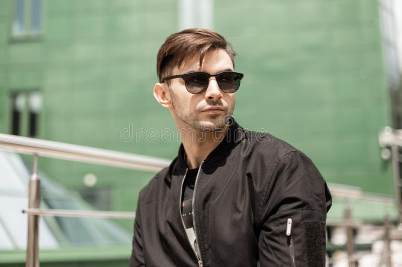 Cool young hipster man with stylish hairstyle in trendy sunglasses in fashionable black jacket outdoors royalty free stock photos