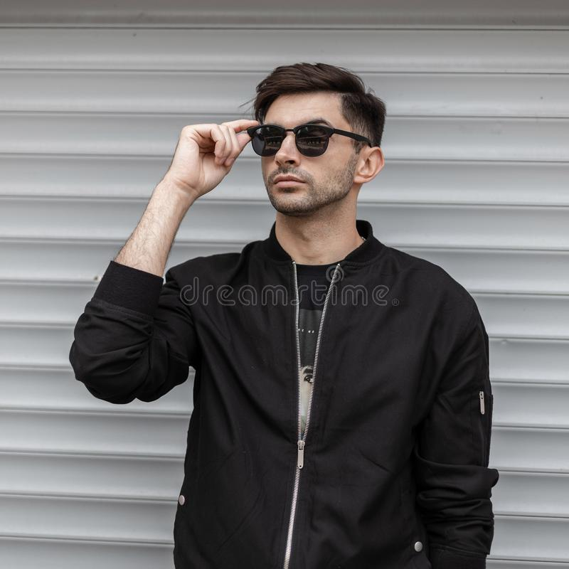 Cool young hipster man in trendy black jacket in stylish sunglasses with a trendy hairstyle is resting. Near a modern white metallic building on the street royalty free stock photo