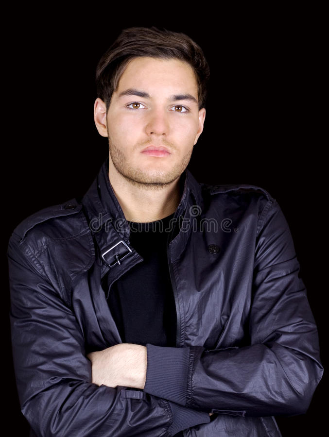 Cool young man. Young man in a leather jacket standing with arms crossed stock photo