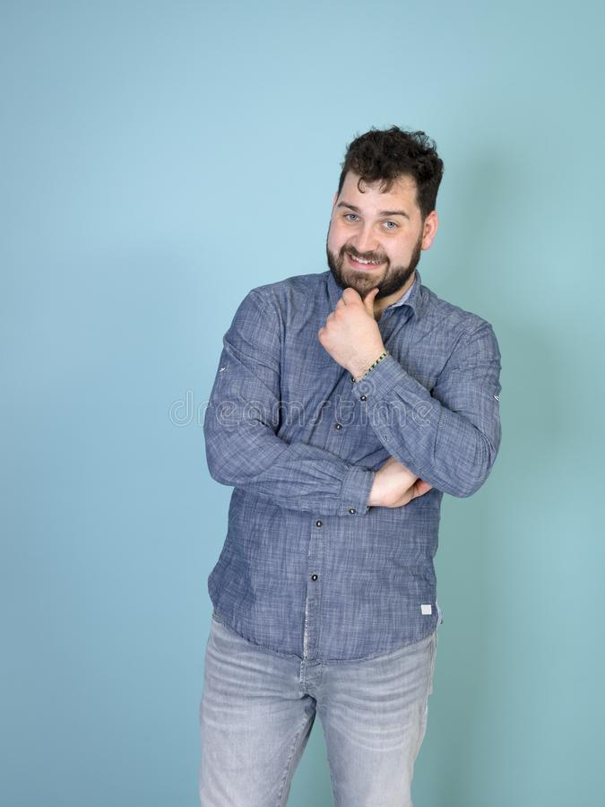 Cool and young man with black hair and black beard posing in front of blue background doing different body exprssions stock image
