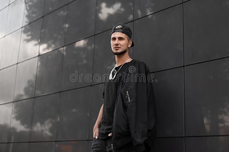 Cool young man hipster with a beard in a black cap in a t-shirt with sunglasses in a fashionable jacket stands near the black wall stock photo