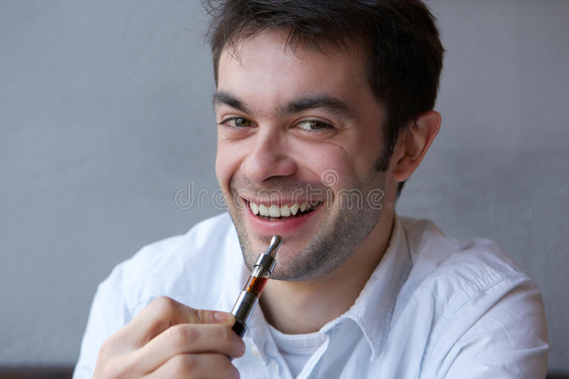 Cool young man holding electric cigarette indoors royalty free stock photo