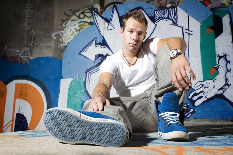 Cool young man showing off shoes royalty free stock photos