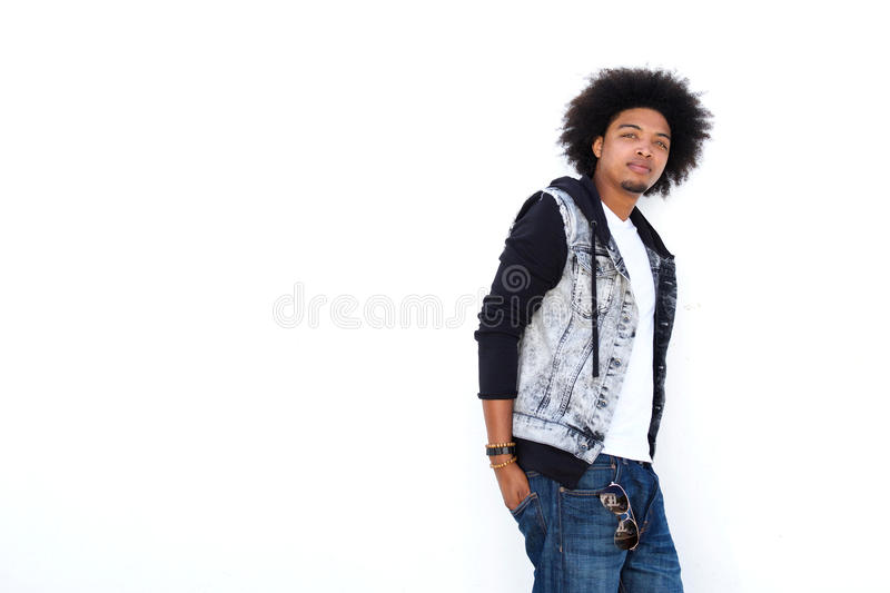 Cool young man standing against white background royalty free stock photography