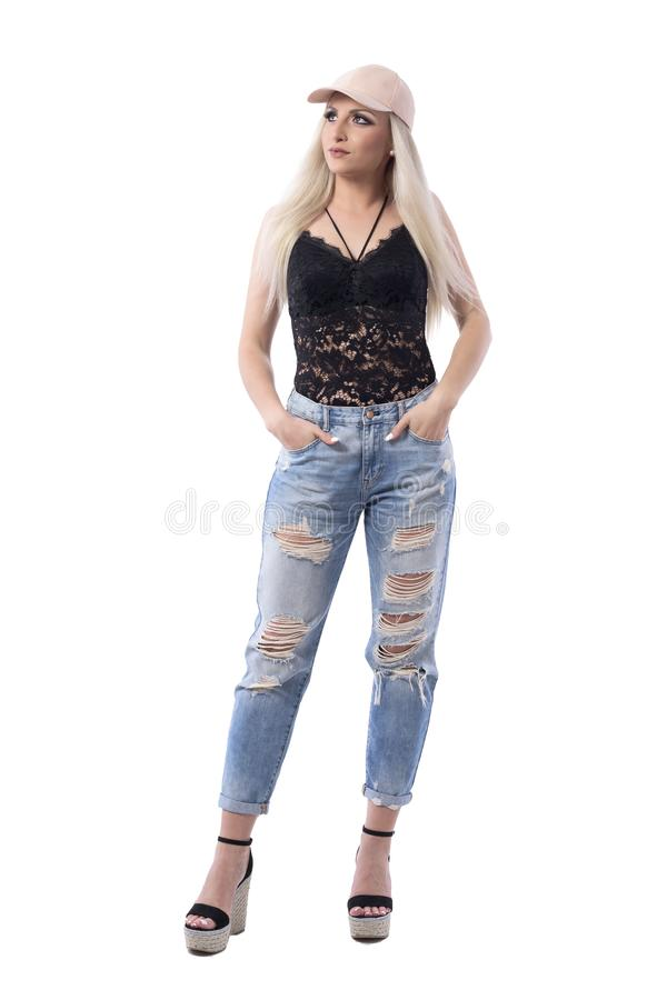Cool young trendy woman in urban style clothes thinking and looking up with hands in pockets stock photo
