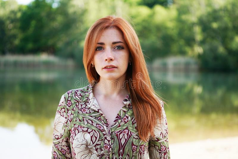 Cool young woman floral pattern ummer dress standing by lake royalty free stock photos