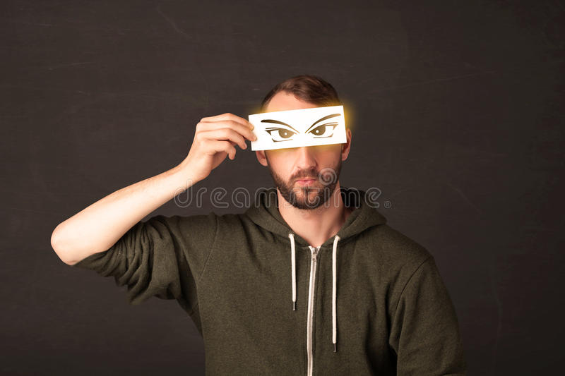 Cool youngster looking with a paper hand drawn eyes. Concept royalty free stock photo