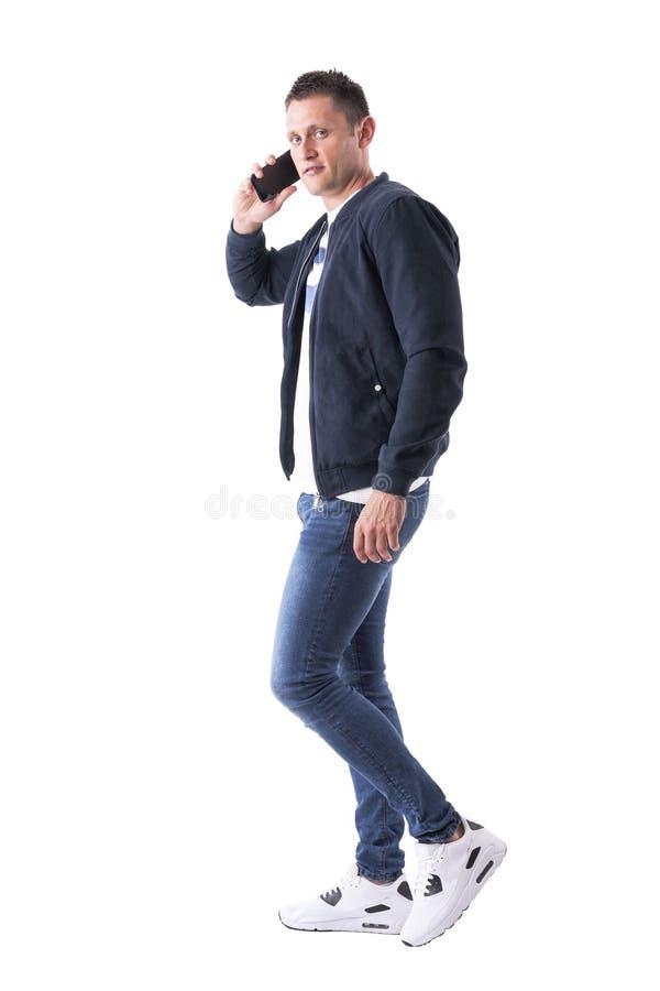 Cool zrelaksowanych ufnych mężczyzna uśmiechy przy kamerą podczas gdy opowiadający na telefonie komórkowym zdjęcie royalty free