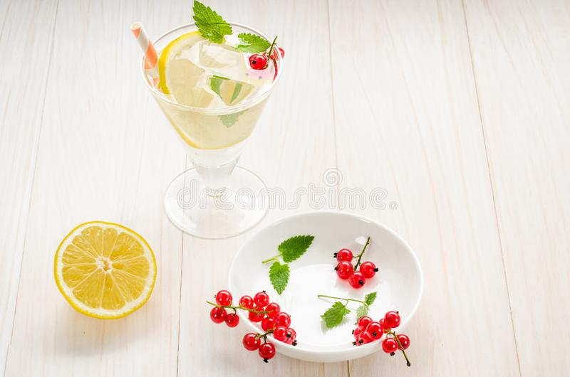 Cooled cocktail with mint, straws, a lemon and red currant/cooled cocktail with mint, straws, a lemon and red currant. Top view royalty free stock photography