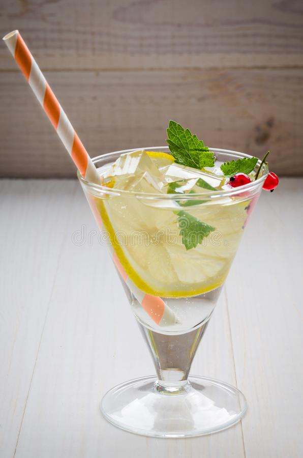 Cooled cocktail with mint, straws and a lemon/cooled cocktail with mint, straws and a lemon. selective focus royalty free stock image
