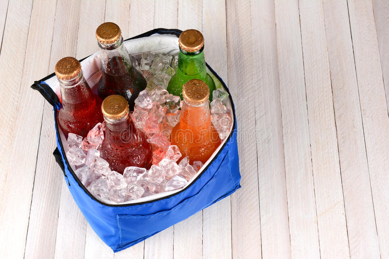 Cooler With Ice and Soda Bottles. High angle shot of a collapsible cooler filled with crushed ice and soda bottles on a rustic wood picnic table. Horizontal royalty free stock image