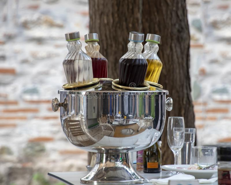Cooling bottles with alcohol on the table set for dinner. The cooler reflects tables and chairs. Greece stock image