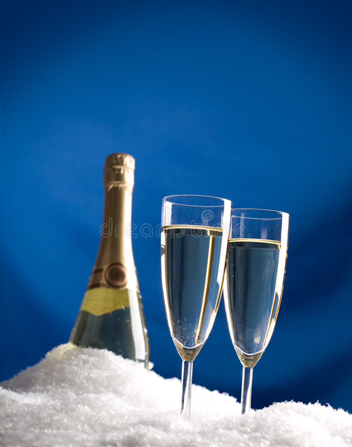Cooling champagne. Image of flutes with champagne and bottle in snow over blue background royalty free stock images