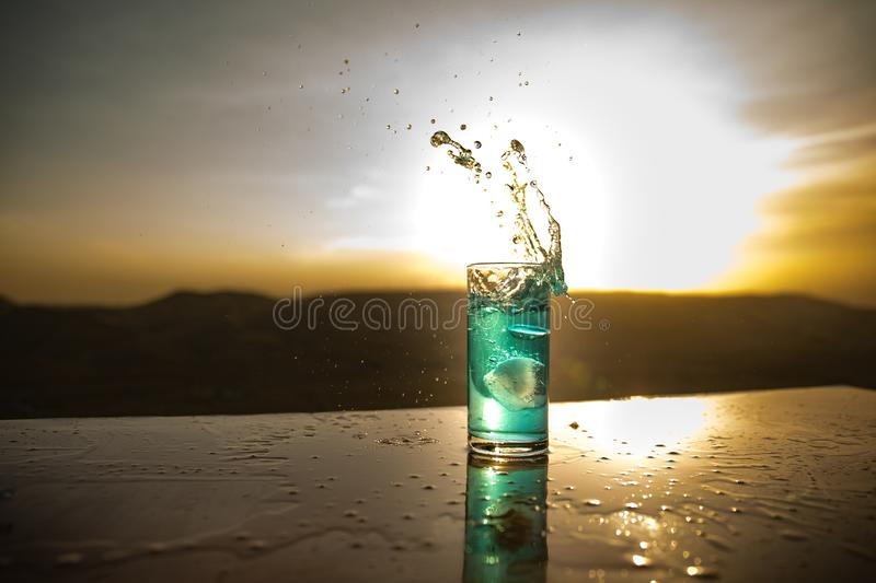 Cooling summer drink concept. Cocktail glasses splashing on sunset. Close up wet glass of cold drink on the terrace stock photo