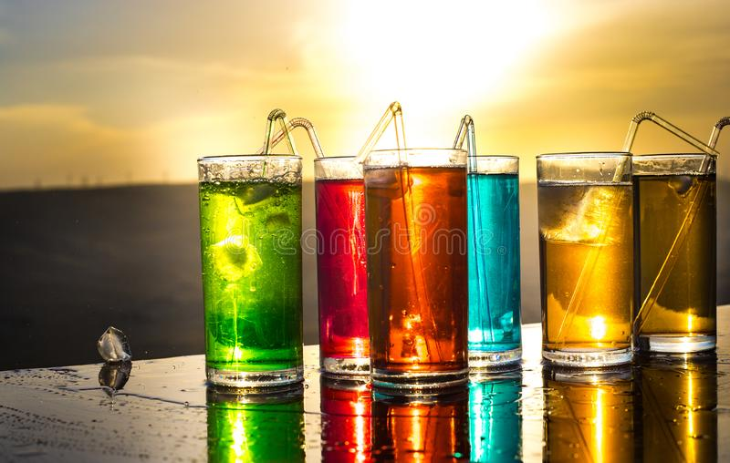 Cooling summer drink concept. Cocktail glasses splashing on sunset. Close up wet glass of cold drink on the terrace royalty free stock photos