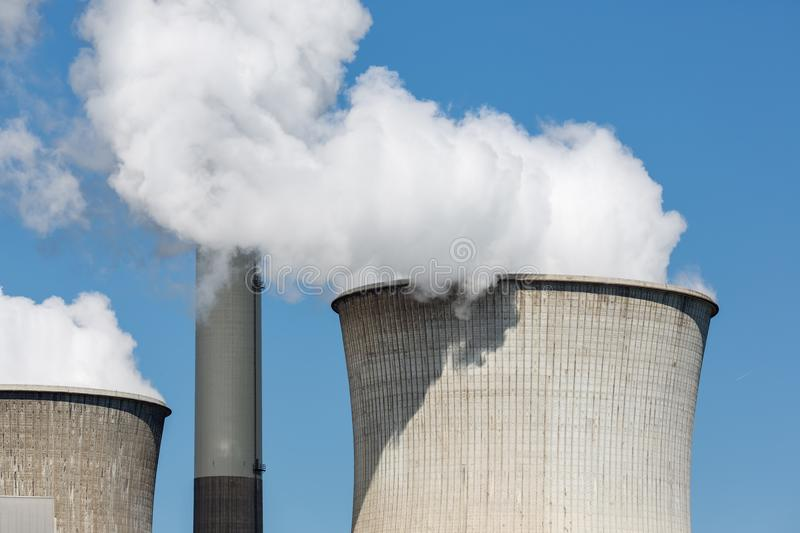 Cooling towers and smokestacks coal fired power plant in Germany. Cooling towers and smokestacks coal fired power plant near lignite mine Garzweiler in Germany stock photos