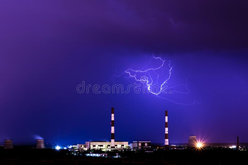 The cooling towers of thermal power station in the rainy night with the lightning. The cooling towers of thermal power station in the rainy night during the stock image