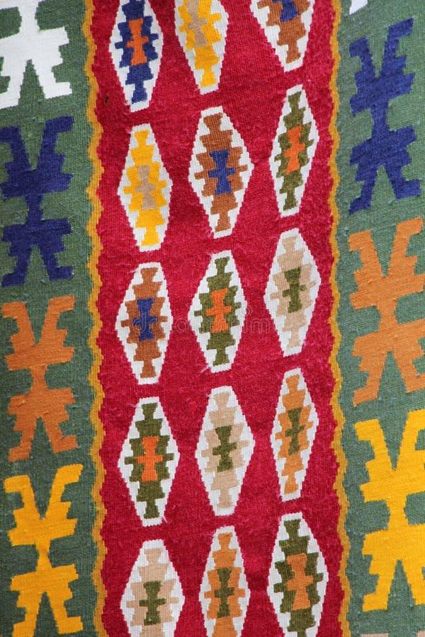 Coooful macedonian hand - gjorda traditionella woolen filtar Ordet FÄRG på kulöra räknare i skarp fokus mot gråa suddiga bokstäve royaltyfri bild