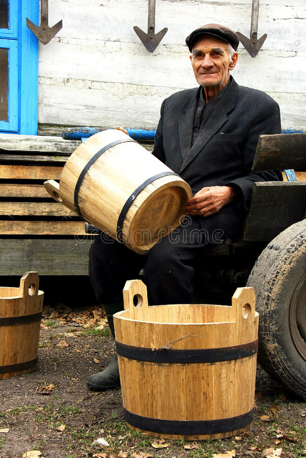 Cooper. Elderly man sitting on a cart and holding a wooden barrel royalty free stock images