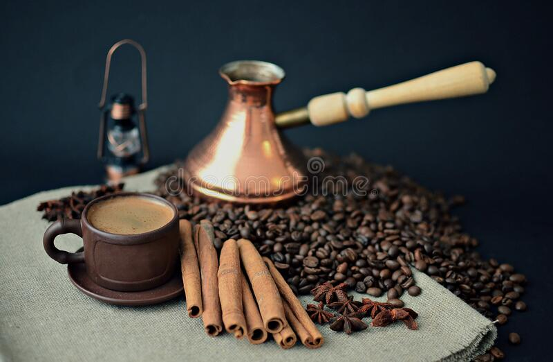Cooper Turkish coffee pot, coffee beans, earthenware coffee Cup, cinnamon sticks, star anise, canvas napkin stock photo