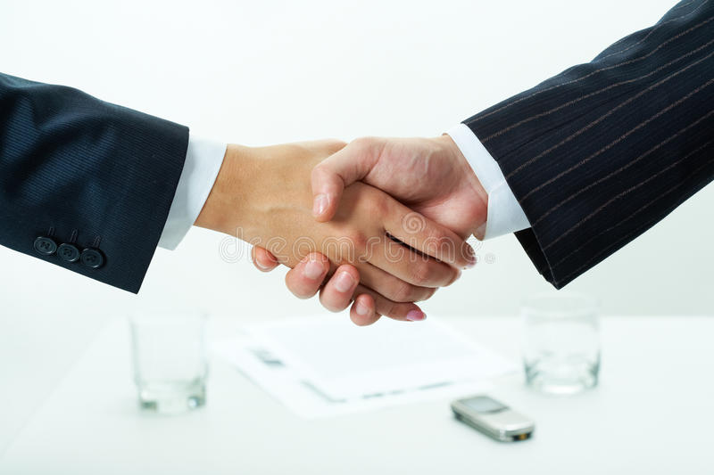 Cooperation. Close-up of two shaking hands over workplace with business documents on it stock images