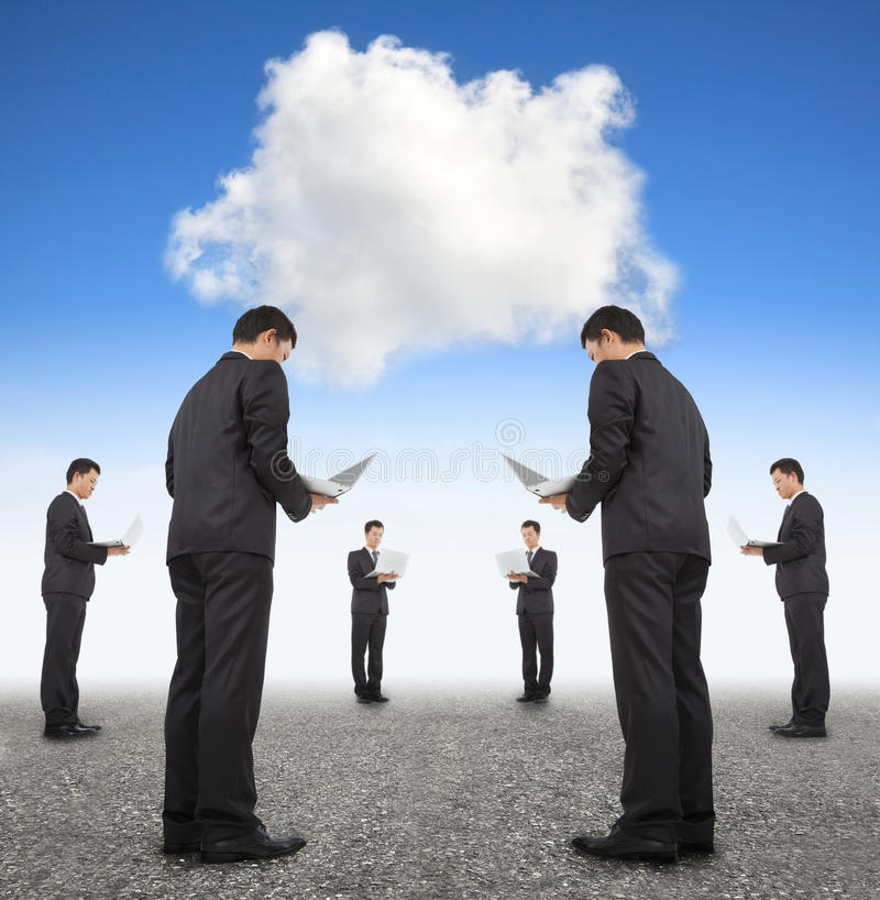 Cooperation business and cloud computing concept. Group of businessman with laptop stock photo