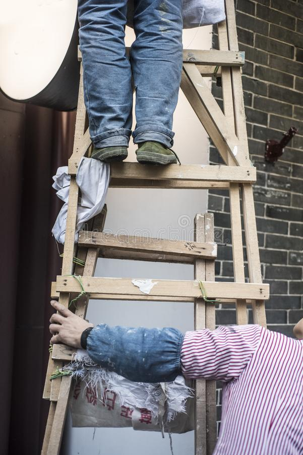 Cooperation, a hand rubbing a wooden ladder, a foot standing on a wooden ladder,. The cooperation of ordinary laborers, two working renovation workers, one hand stock photos