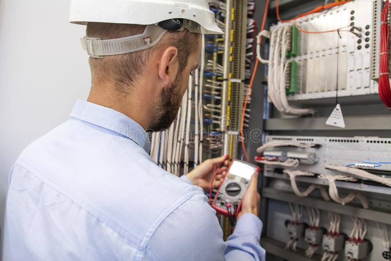 Coordenador adulto novo do construtor do eletricista que inspeciona o equipamento bonde na caixa do fusível da distribuição foto de stock