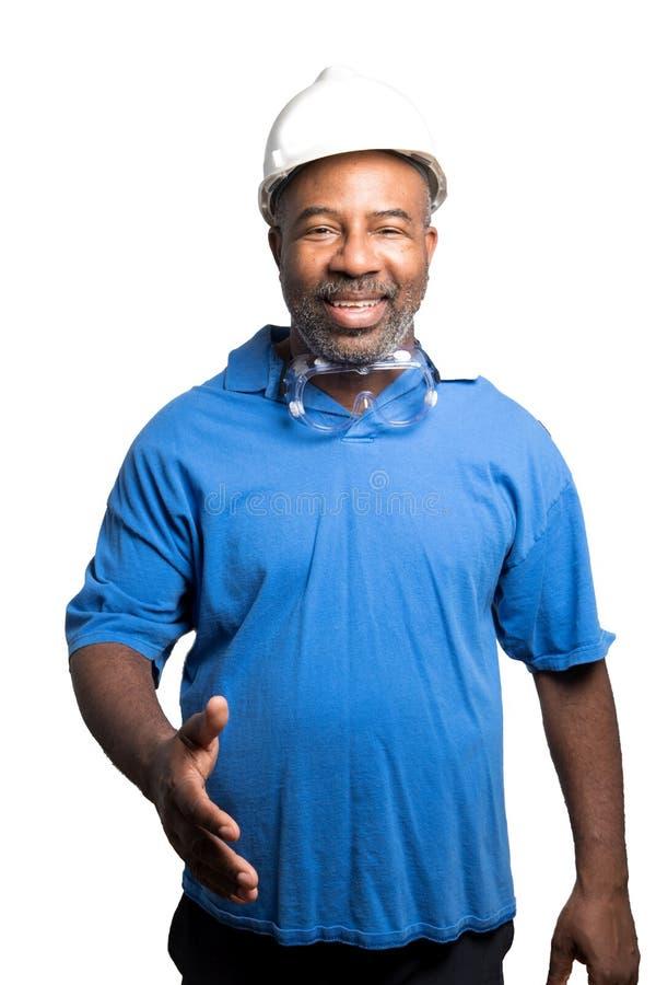 Coordenador afro-americano com vidros de segurança e capacete de segurança que alcança para fora para agitar as mãos no fundo bra imagens de stock royalty free