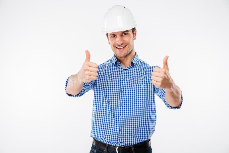 Coordenador alegre do homem novo no capacete da construção que mostra os polegares acima imagens de stock royalty free