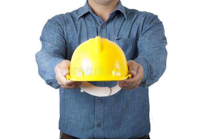 Coordenador, camisa azul do desgaste da arquitetura e para guardar o capacete de segurança amarelo no fundo do isolado foto de stock