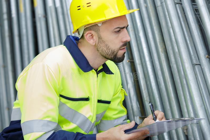 Coordenador com capacete amarelo que escreve para baixo na prancheta fotografia de stock